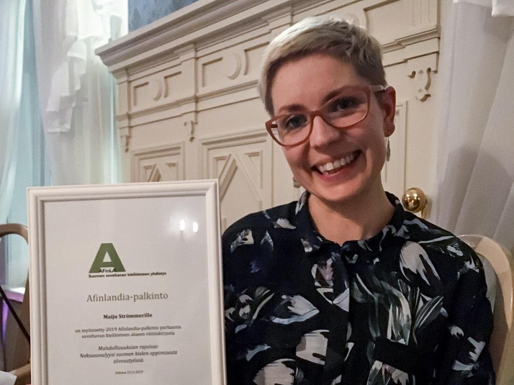 Maiju Strömmer pitää kädessään Afinlandia-palkinto-diplomia.