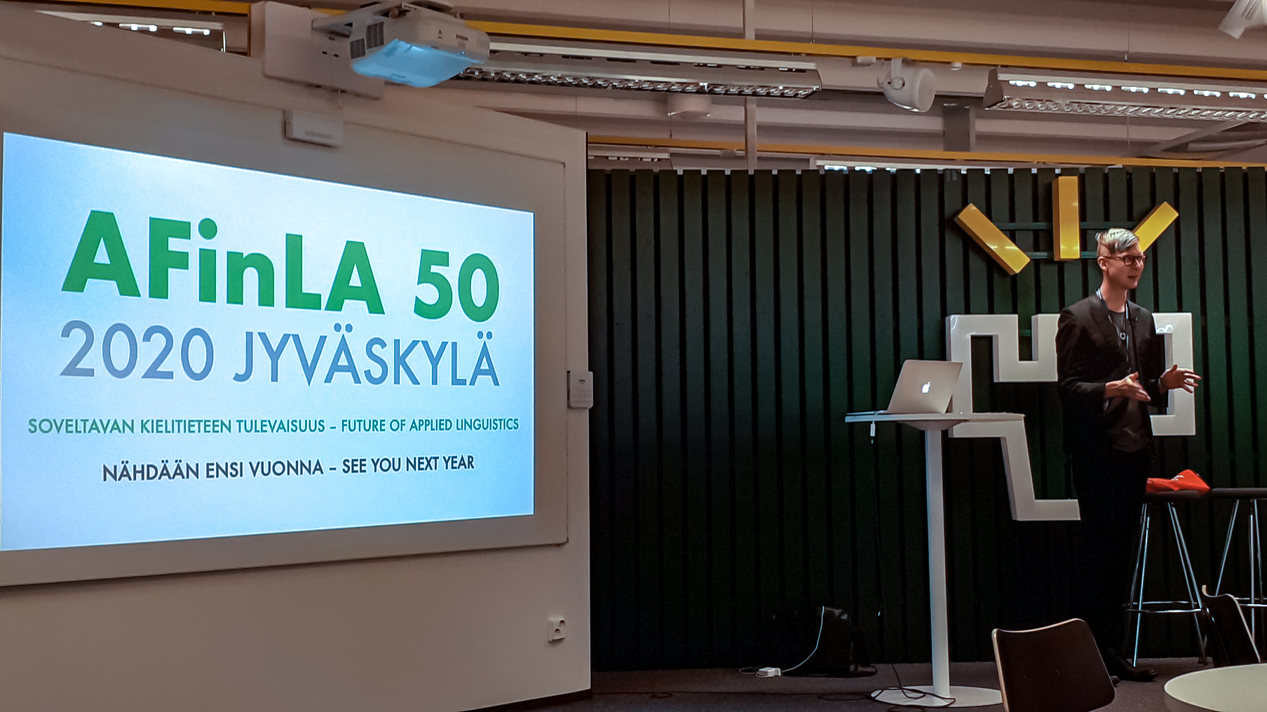 Juha Jalkanen pitämässä puhetta ja taustalla on iso näyttö.