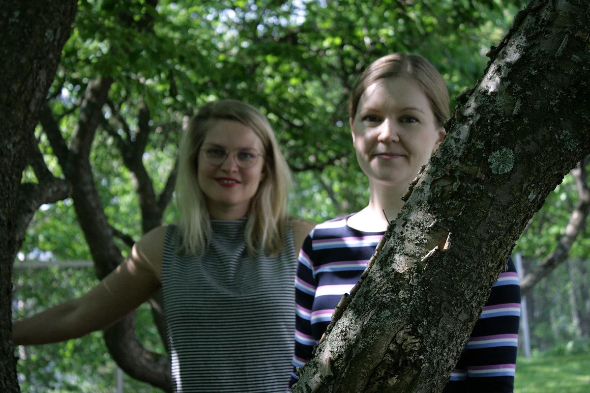 Elina Late ja Laura Korkeamäki puiden keskellä katsoen kameraan.