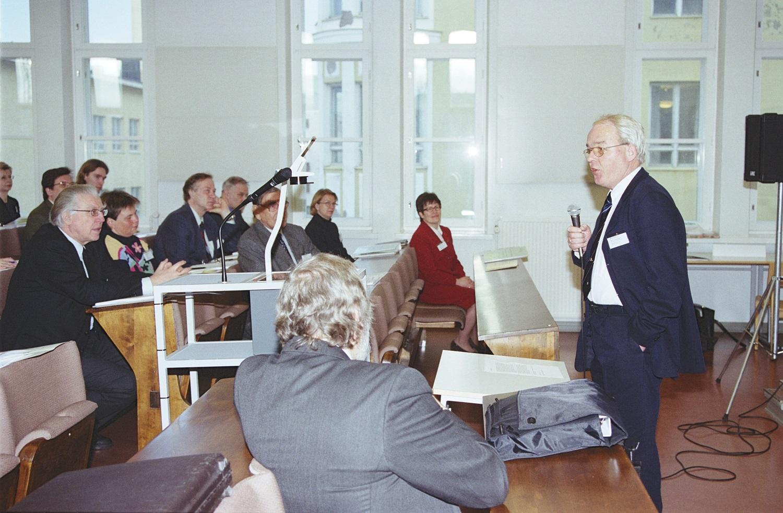 Marcel Van den Broecke seisoo oikealla pitämässä seminaaripuhetta.