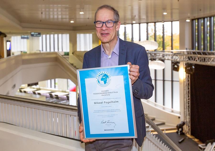 Kuvassa Mikael Fogelholm Vuoden tiedekongressidiplomin kanssa