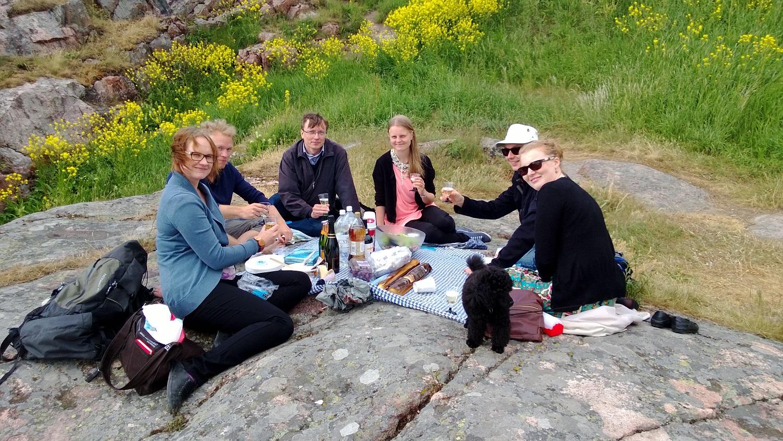 Seuran vuoden 2013 hallitus istuu kalliolla piknikillä.