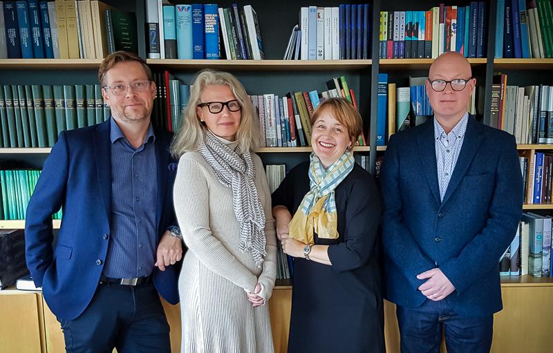 Kuvassa neljä henkilöä seisoo kirjahyllyjen edustalla.