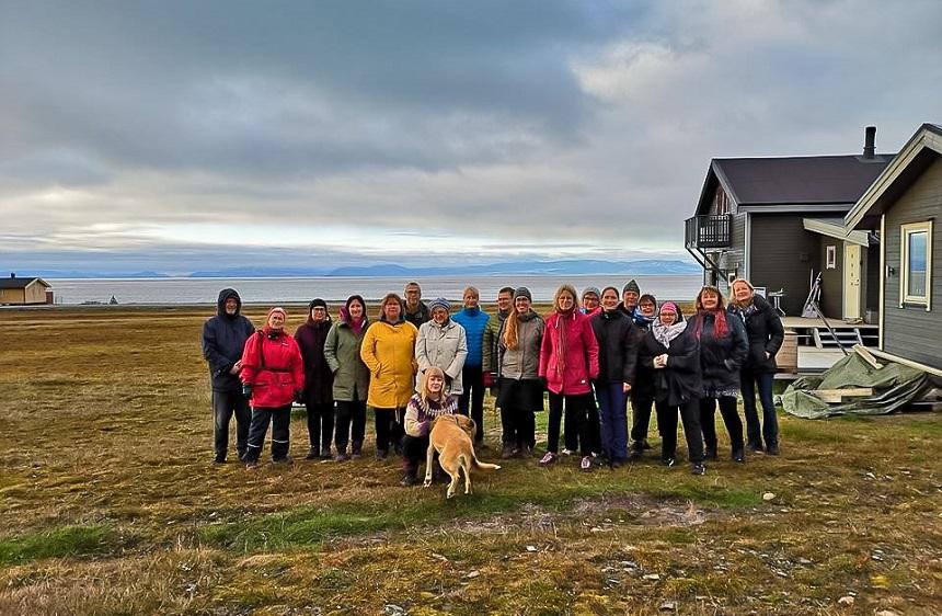 Joukko ihmisiä ryhmäkuvassa ison talon ja jylhän maiseman edustalla.