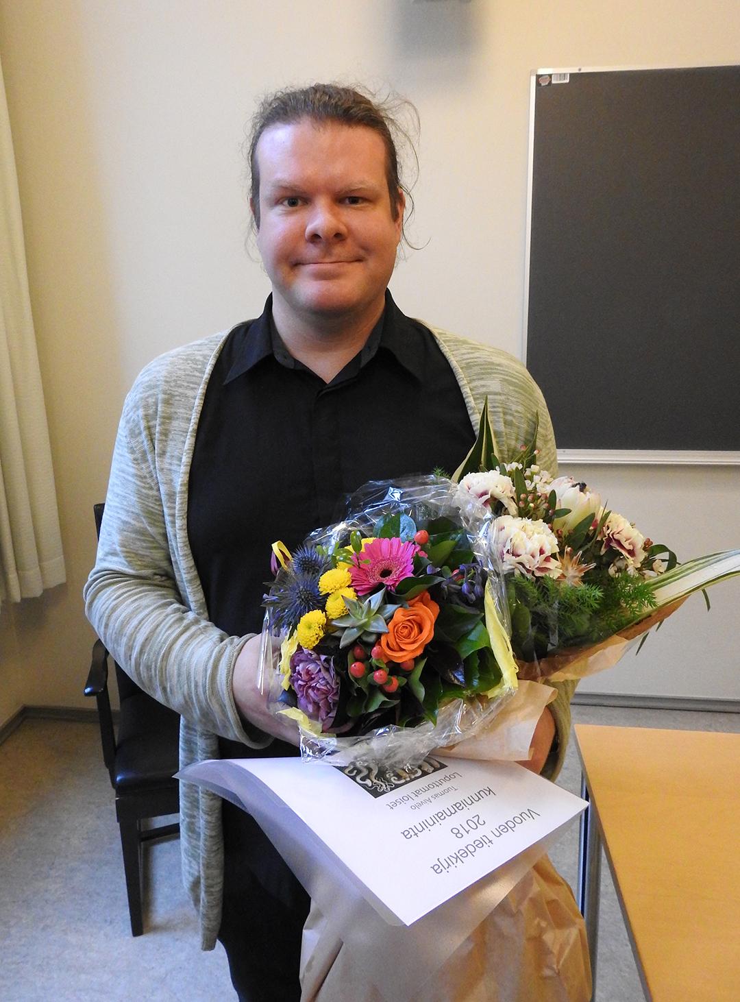 Tuomas Aivelo kukkien ja diplomin kanssa.