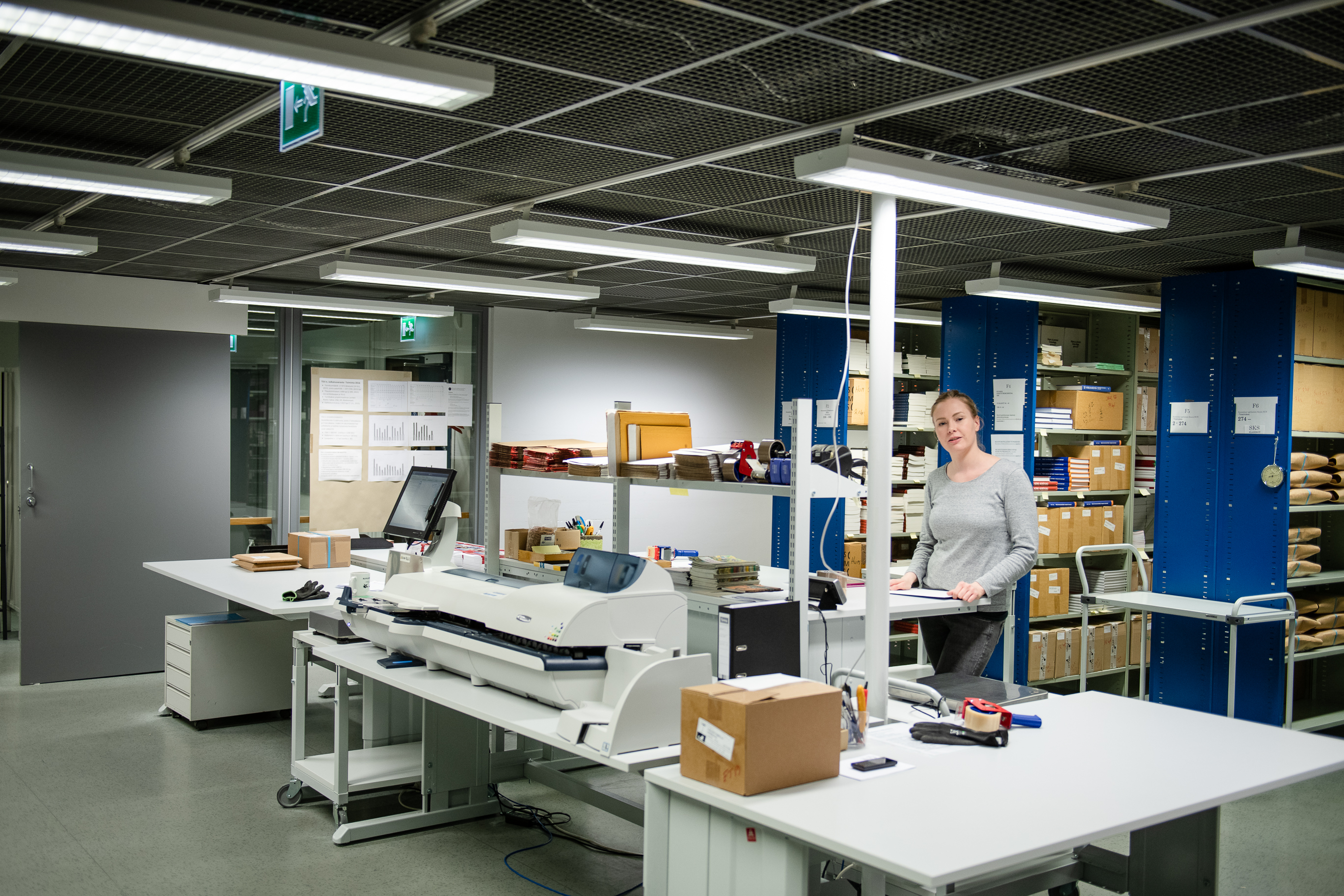 Julkaisuvaraston pakkaamo, kyllyjä ja pöytätaso, jossa paljon erilaista tavaraa ja laitteistoa.