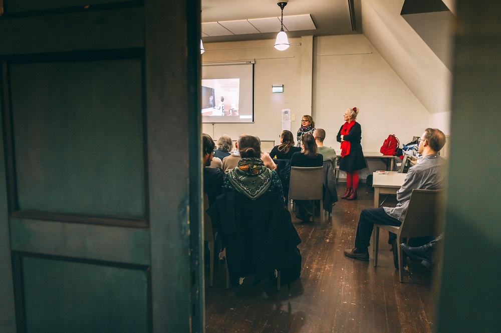 Ihmisiä kuuntelemassa luentoa salissa, kuvattuna salin takaosasta ovelta.