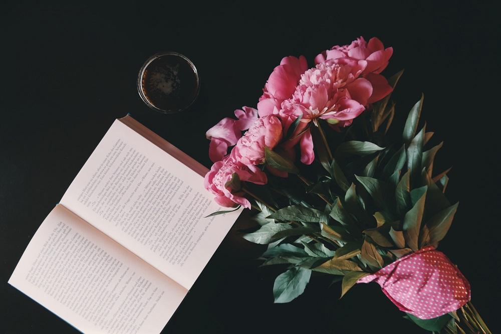 Uutisen kuvituskuvassa kirja ja kukkakimppu.