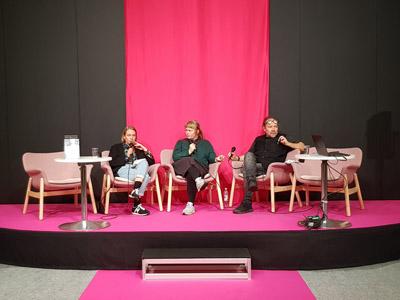 Kolme henkilöä keskustelee lavalla yleisön edessä.