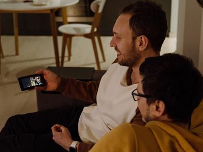 Kaksi ihmistä istuu sohvalla ja katsoo esitystä toisen puhelimesta.