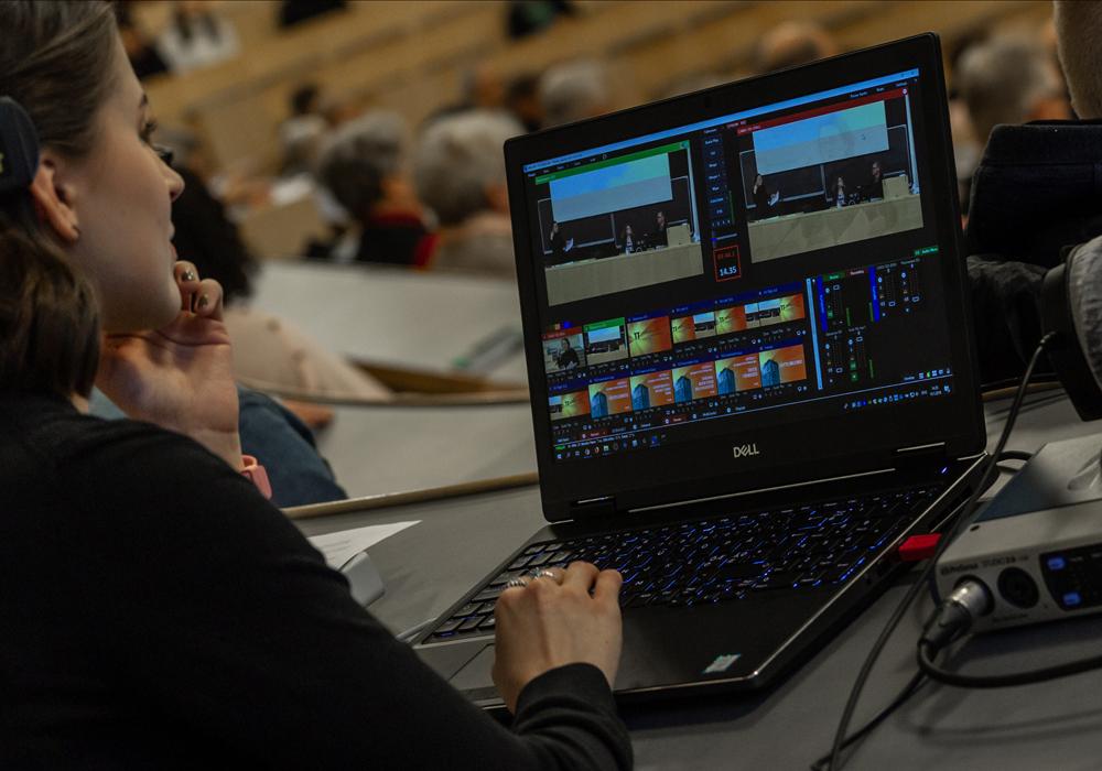 Kuvasta osittain pois rajattu henkilö tarkkailee tietokoneen ruudulta luennon tallentumista videolle. Taustalla näkyy käynnissä oleva luento ja luentosalia.