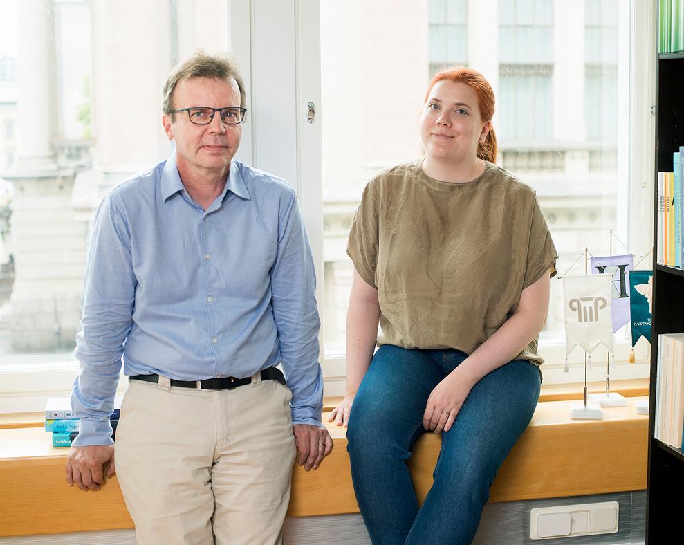 Mandi Vermilä ja Ilari Hetemäki istuvat neuvotteluhuoneen ikkunalaudalla. Taustalla näkyy Kansallisarkiston julkisivua.