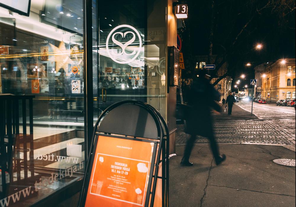Vy över Snellmansgatan i Helsingfors i mörkret. Ljusen avspeglas i Vetenskapsbokhandelns fönster.
