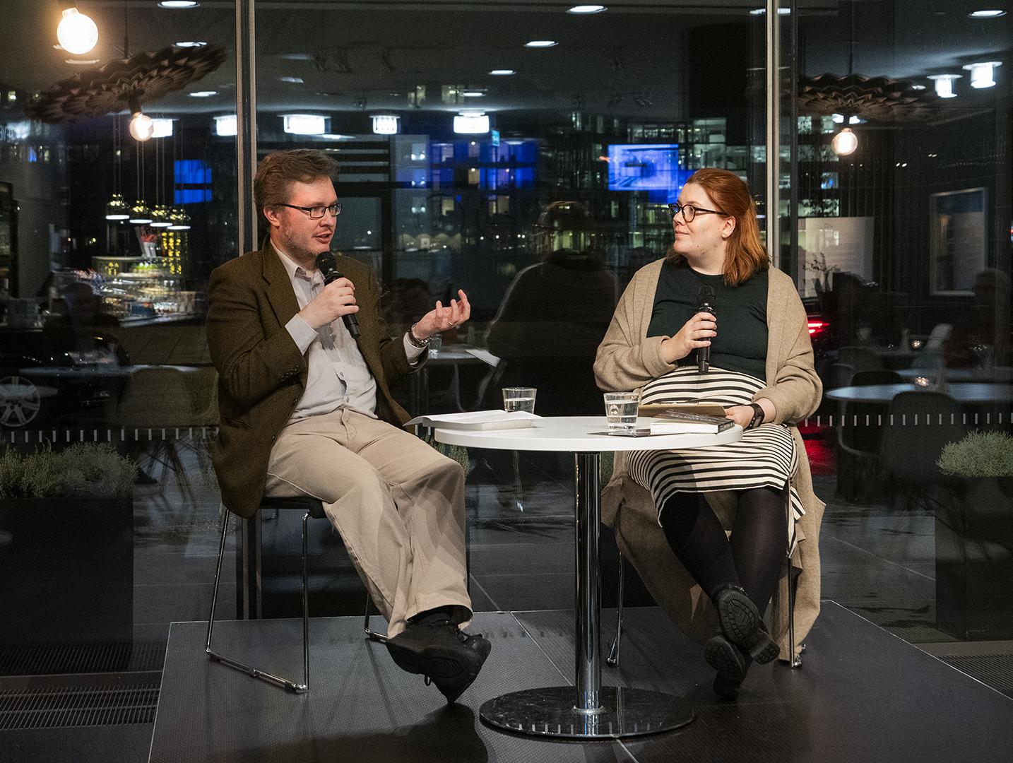 Haastateltava ja haastattelija istuvat tuoleilla lavalla ja keskustelevat.
