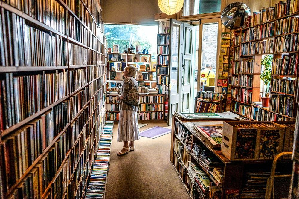 Henkilö katselemassa kirjoja kirjakaupassa.