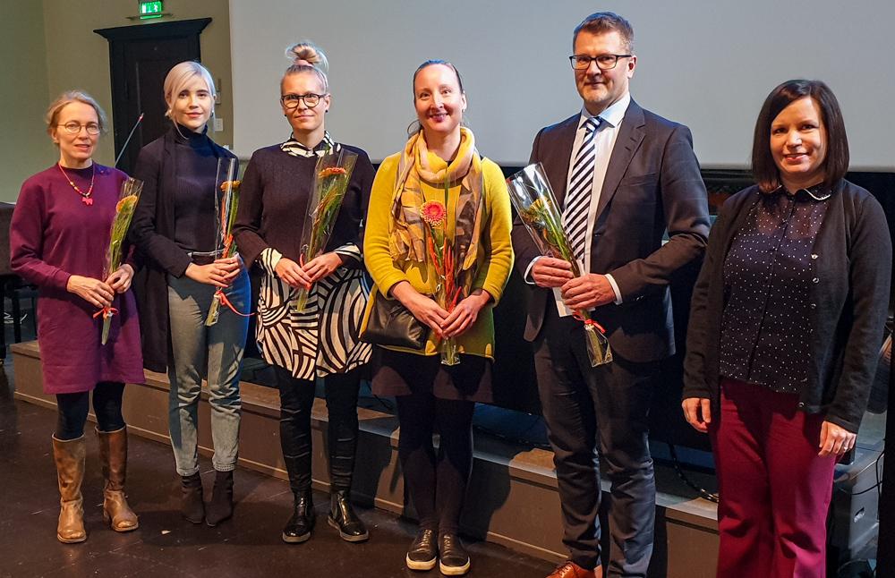 Kuusi henkilöä seisoo, osalla kukkia käsissään.
