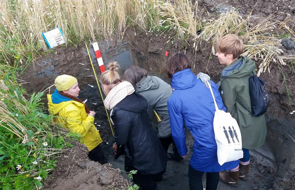 Ihmiset seisovat maakuopassa tutkimassa Liedon savimaaprofiilia.