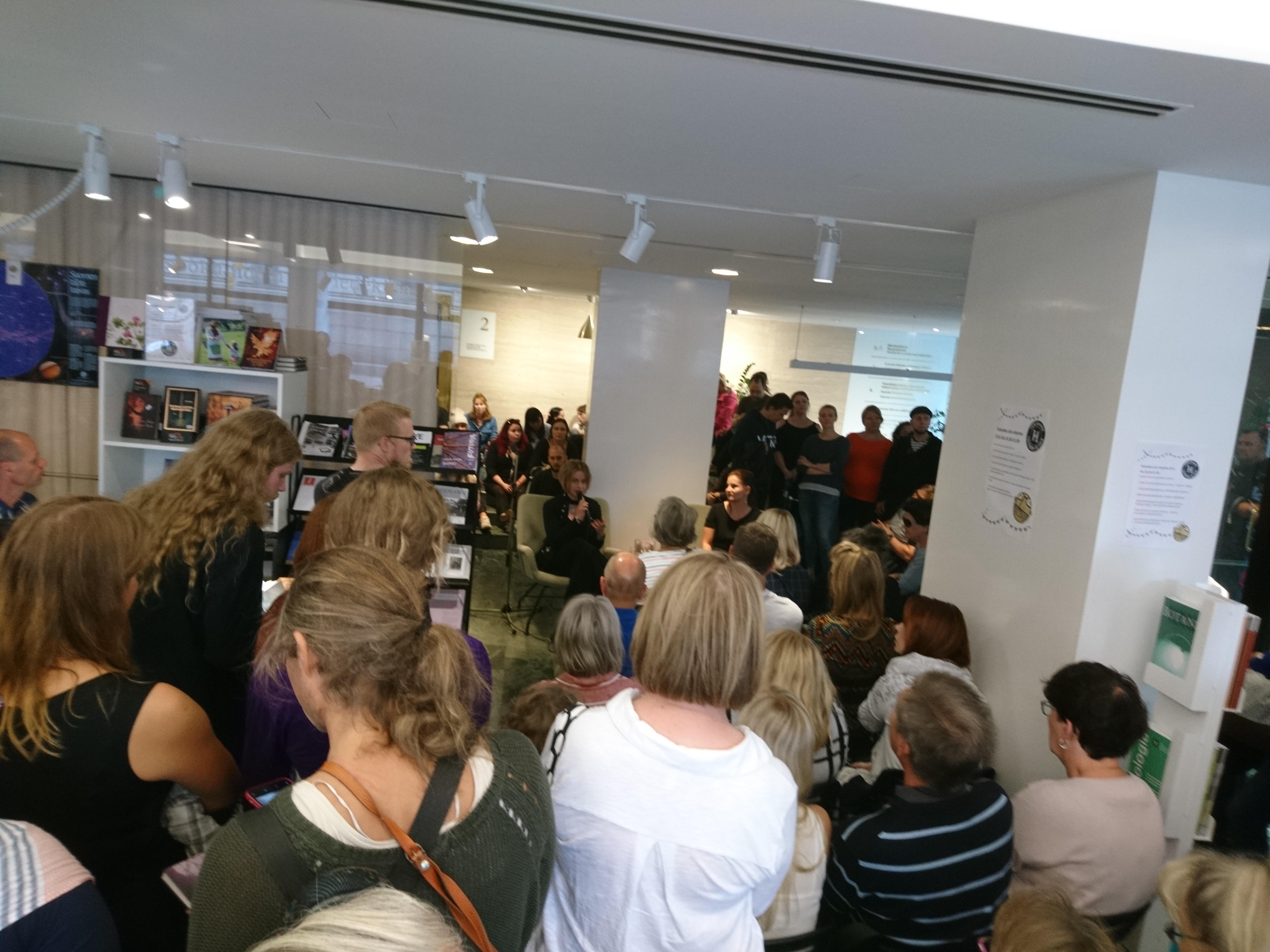 Yleisöä pakkautunut Tiedekirjan tiloihin kuuntelemaan esitystä.
