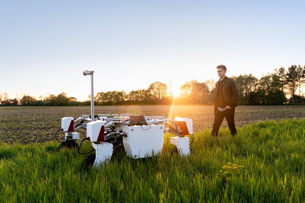 Miespuolinen insinööri pellolla vierellään maatalousrobotti.