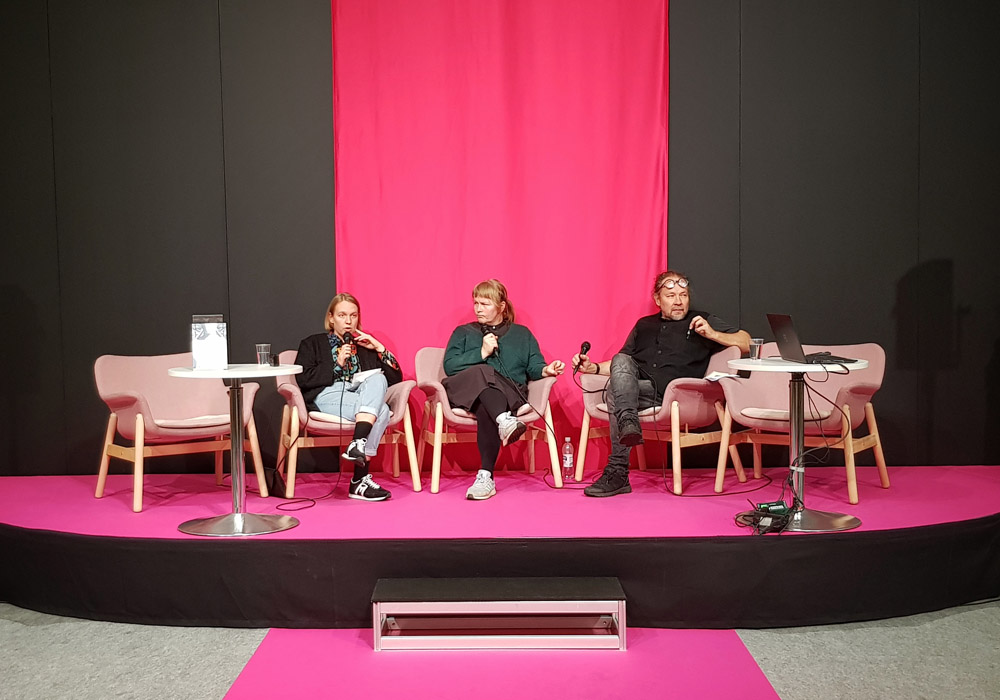Lavalla on kolme henkilöä, jotka keskustelevat yleisön edessä.