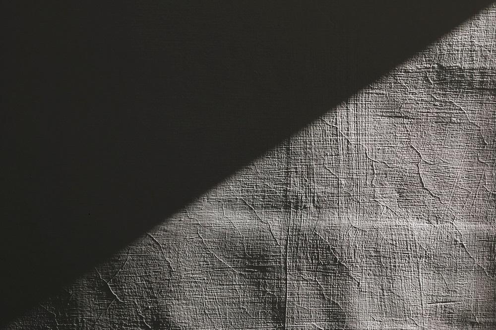Valo ja varjo kohtaavat toisensa vaaleaa pintaa vasten.
