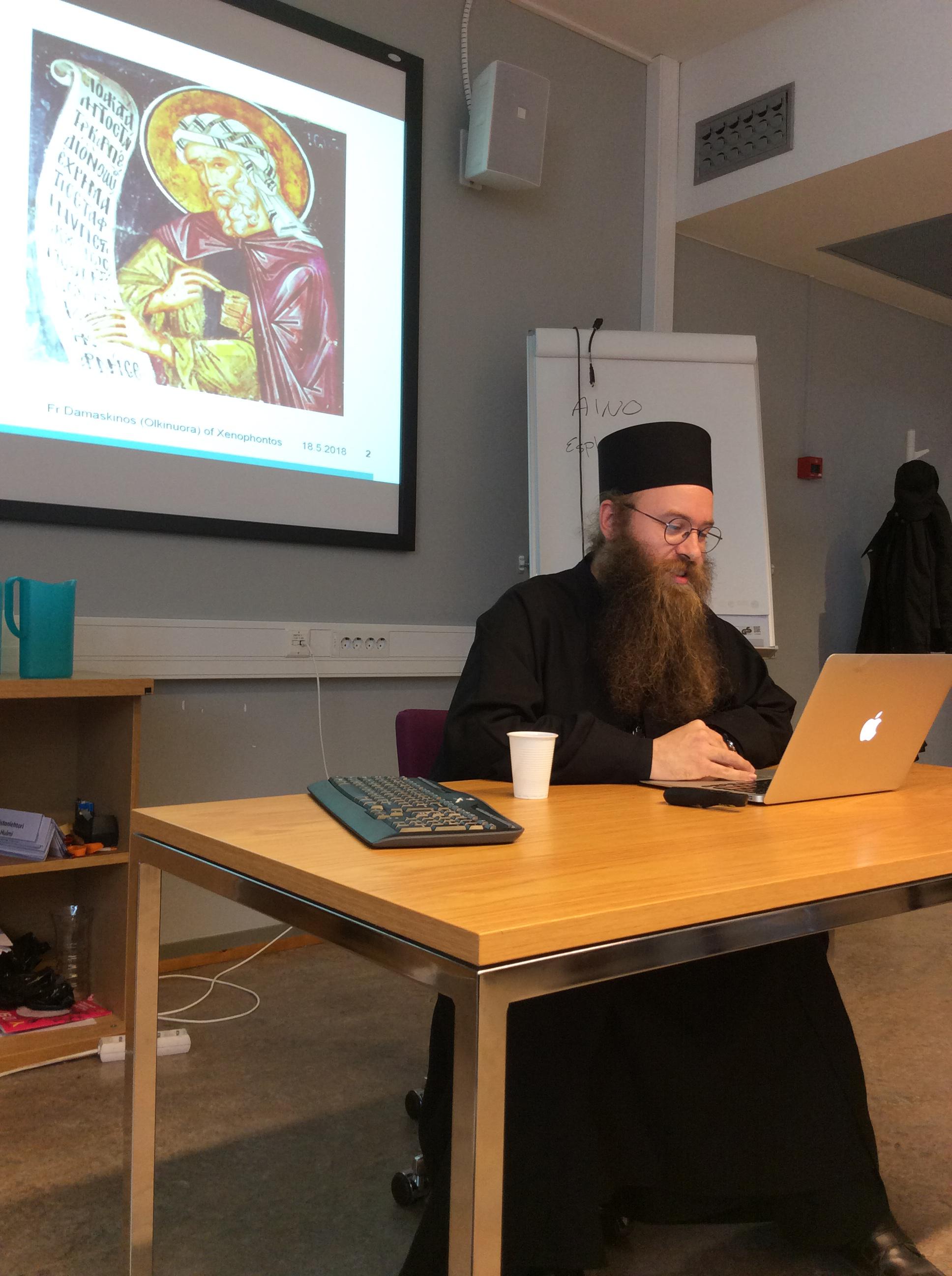 Pappismunkin asuun pukeutunut henkilö istuu pöydälle asetetun tietokoneen edessä.