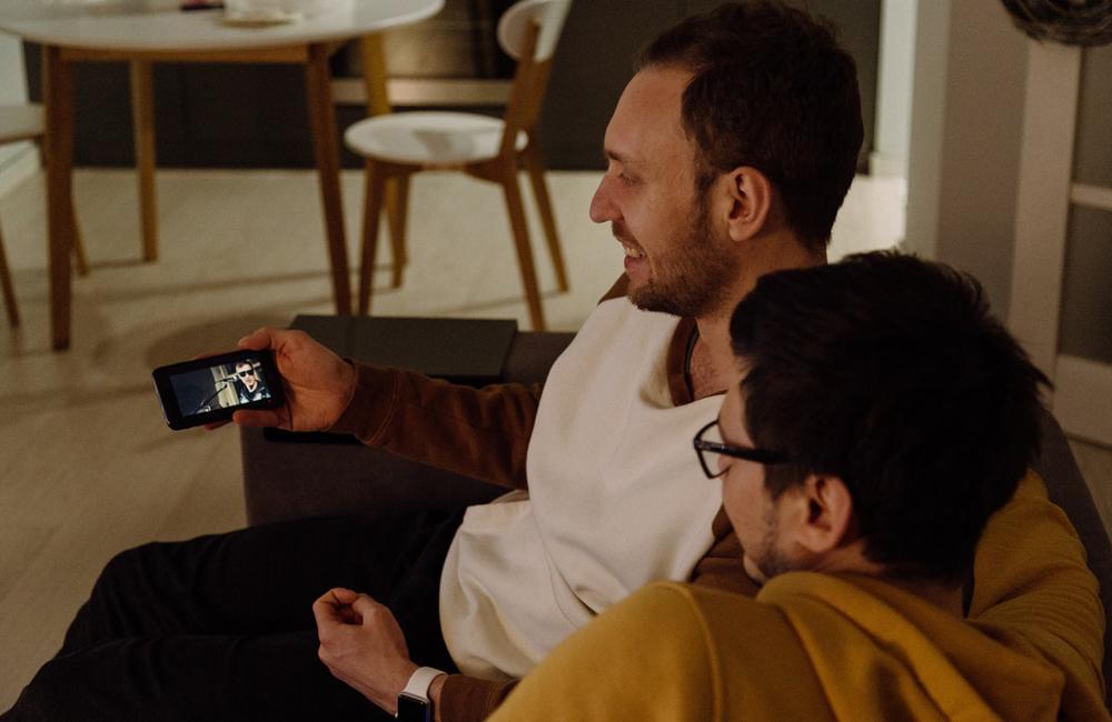 Kaksi ihmistä katselevat sohvalla esitystä toisen puhelimesta.