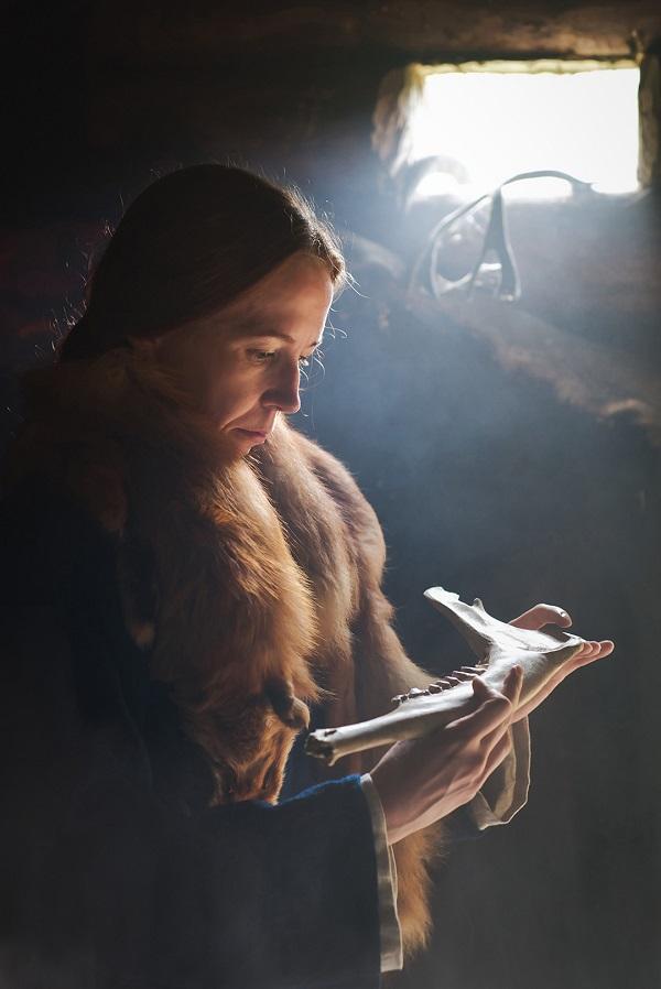 Ulla Moilasen teos Noiat noitui kyyt kiroili kpssa kettupuuhka kaulassa nainen katselee käsissään olevaa eläimen kallon palasta.